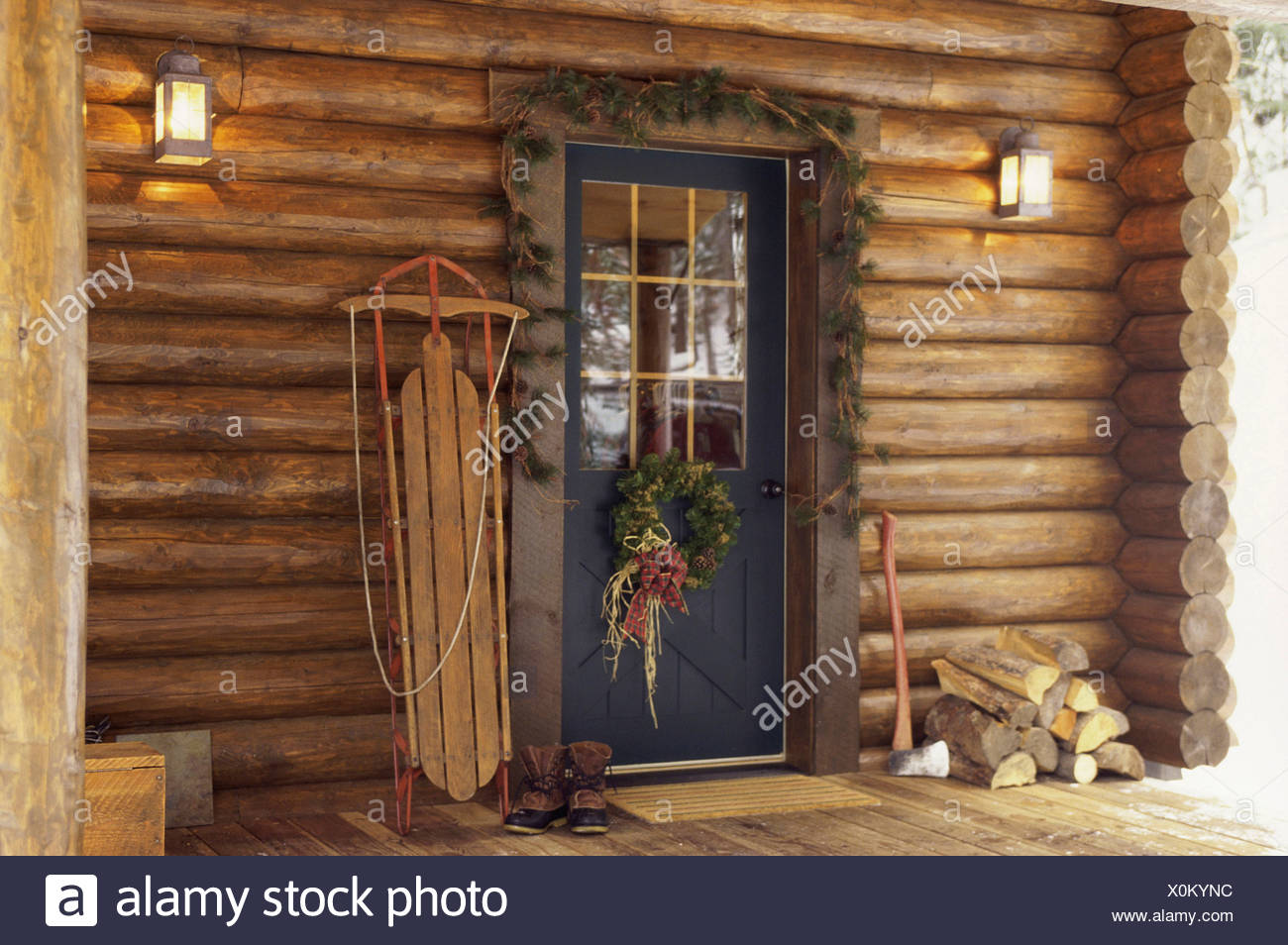 christmas decorations around a log cabin door