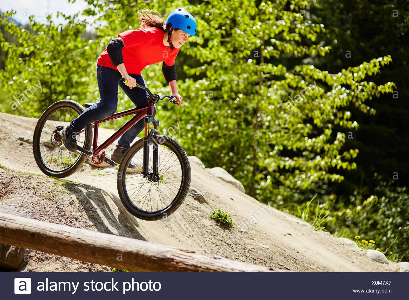 Young female bmx biker speeding down rocks in forest - Stock Image