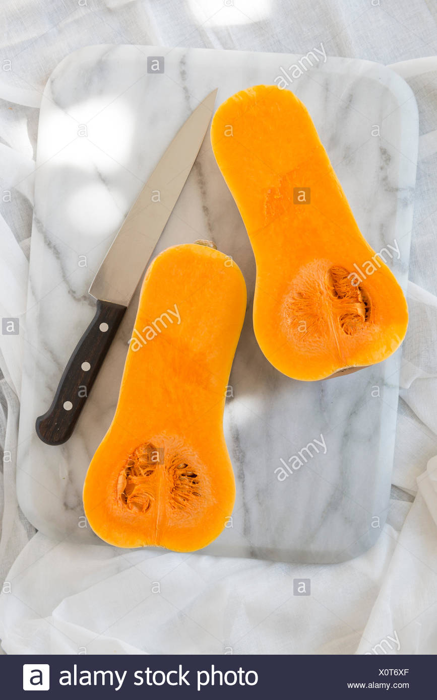Sliced butternut squash on a marble chopping board. - Stock Image