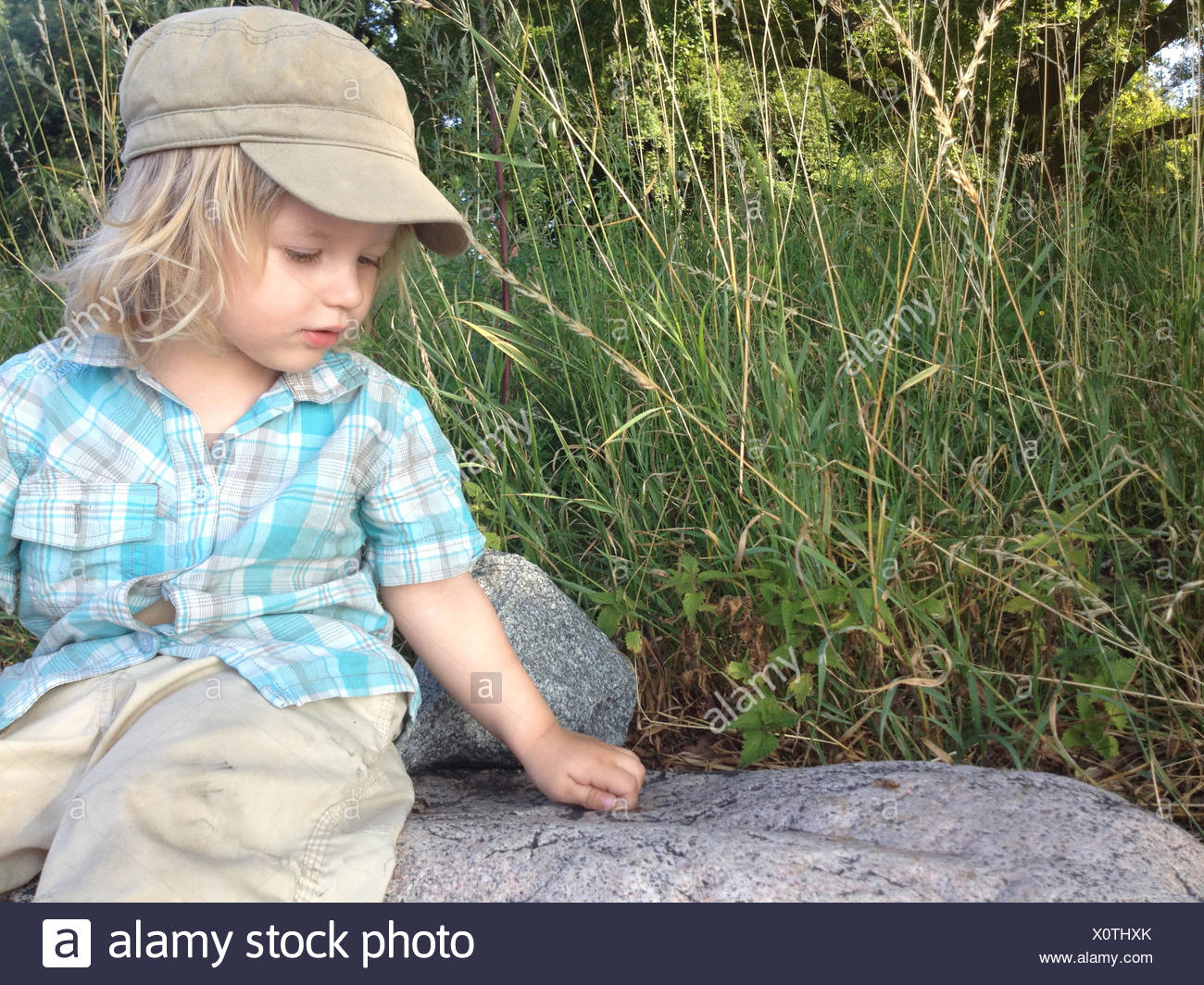Young Boy Playing On A Rock - Stock Image