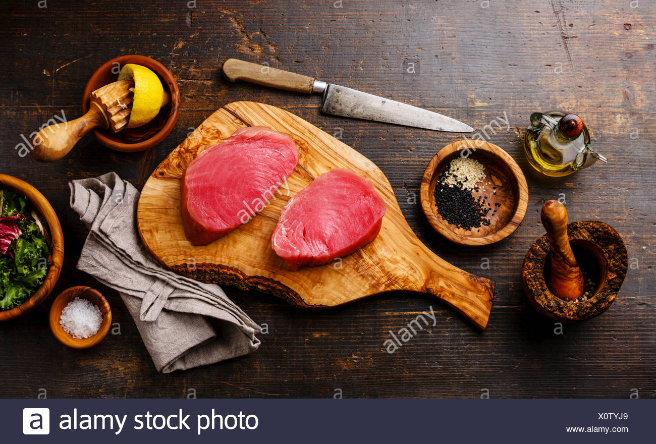 Raw tuna steaks fillet with lemon and sesame on olivewood cutting board on dark wooden background - Stock Image