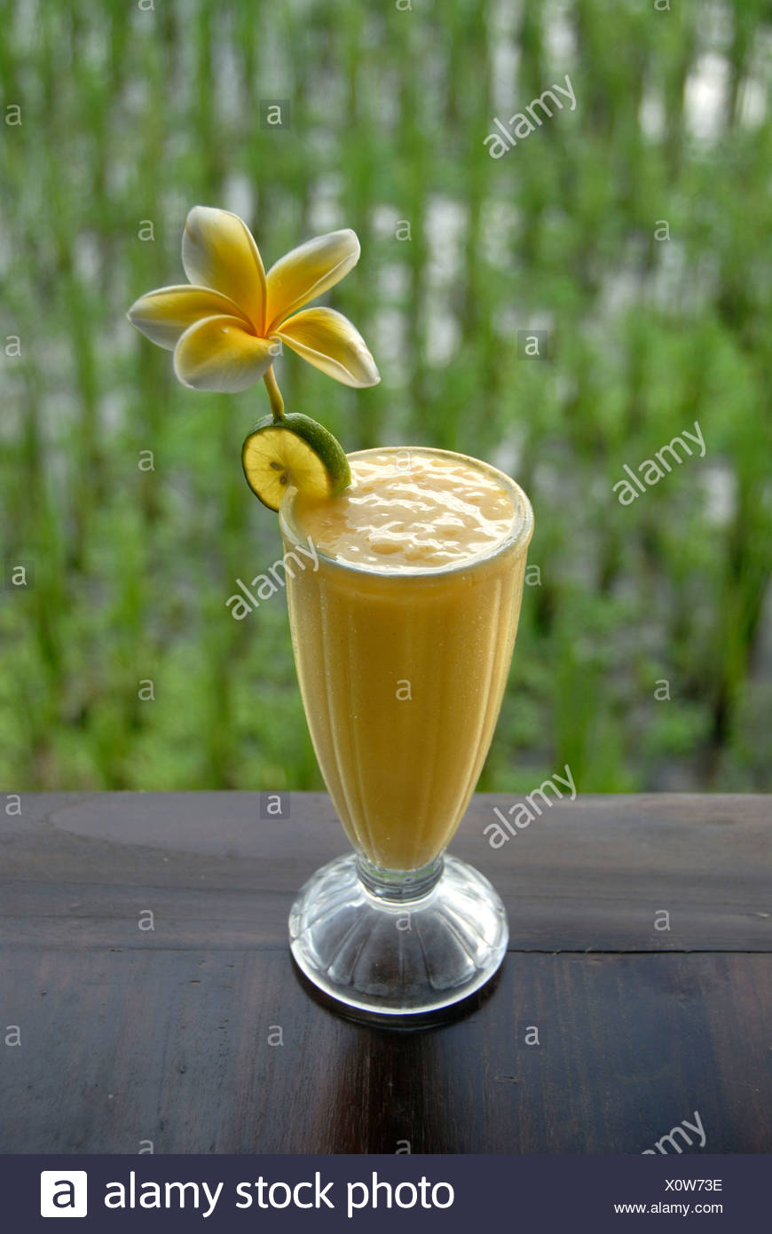 Soft drink, mango smoothie in a glass decorated with flowers, in front of a rice field in Ubud, Bali, Indonesia, Southeast Asia - Stock Image