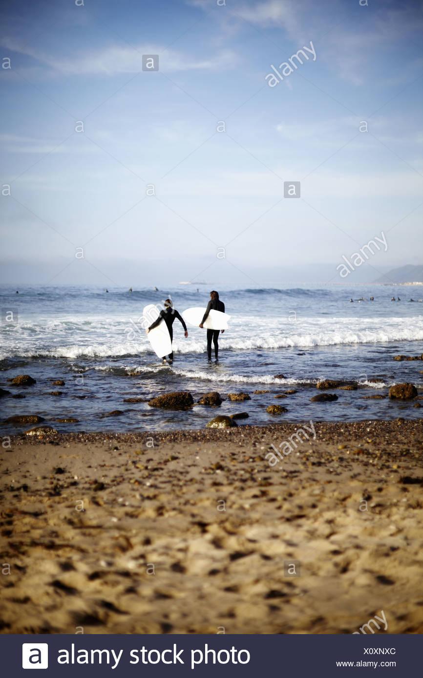 Massachusetts USA Two surfers seashore inspecting the waves USA - Stock Image