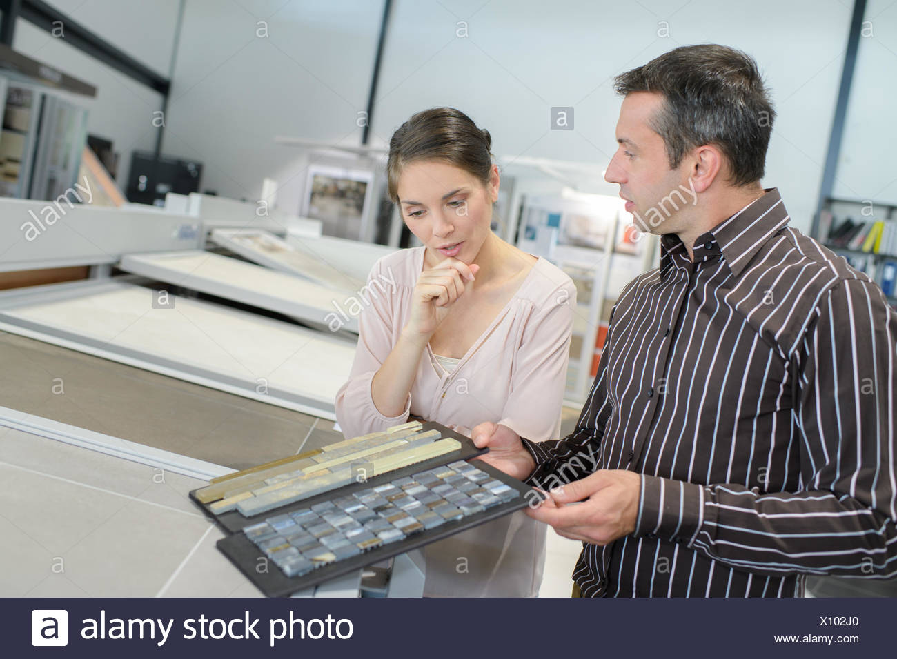 Couple pointing at ceramic tile for bathroom floor in store stock couple pointing at ceramic tile for bathroom floor in store dailygadgetfo Image collections