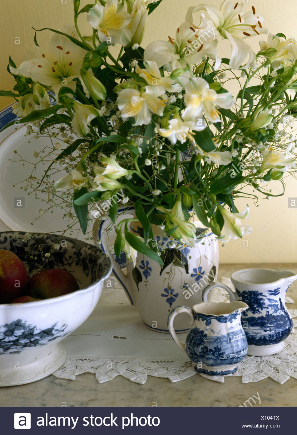 Still Life Of Cream Lilies In Old Blue Patterned Jug On Table With