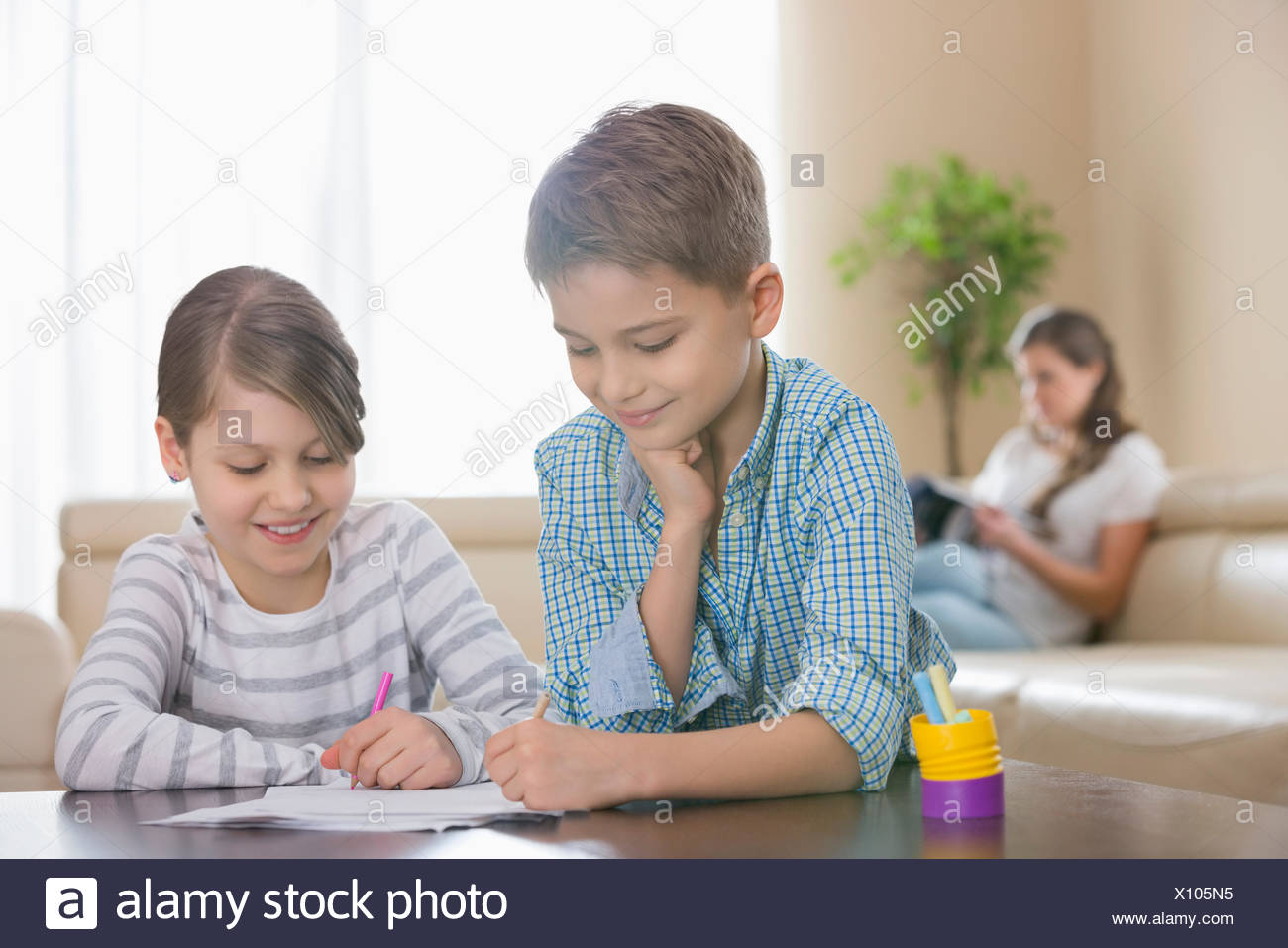Siblings drawing together at table with mother in background - Stock Image