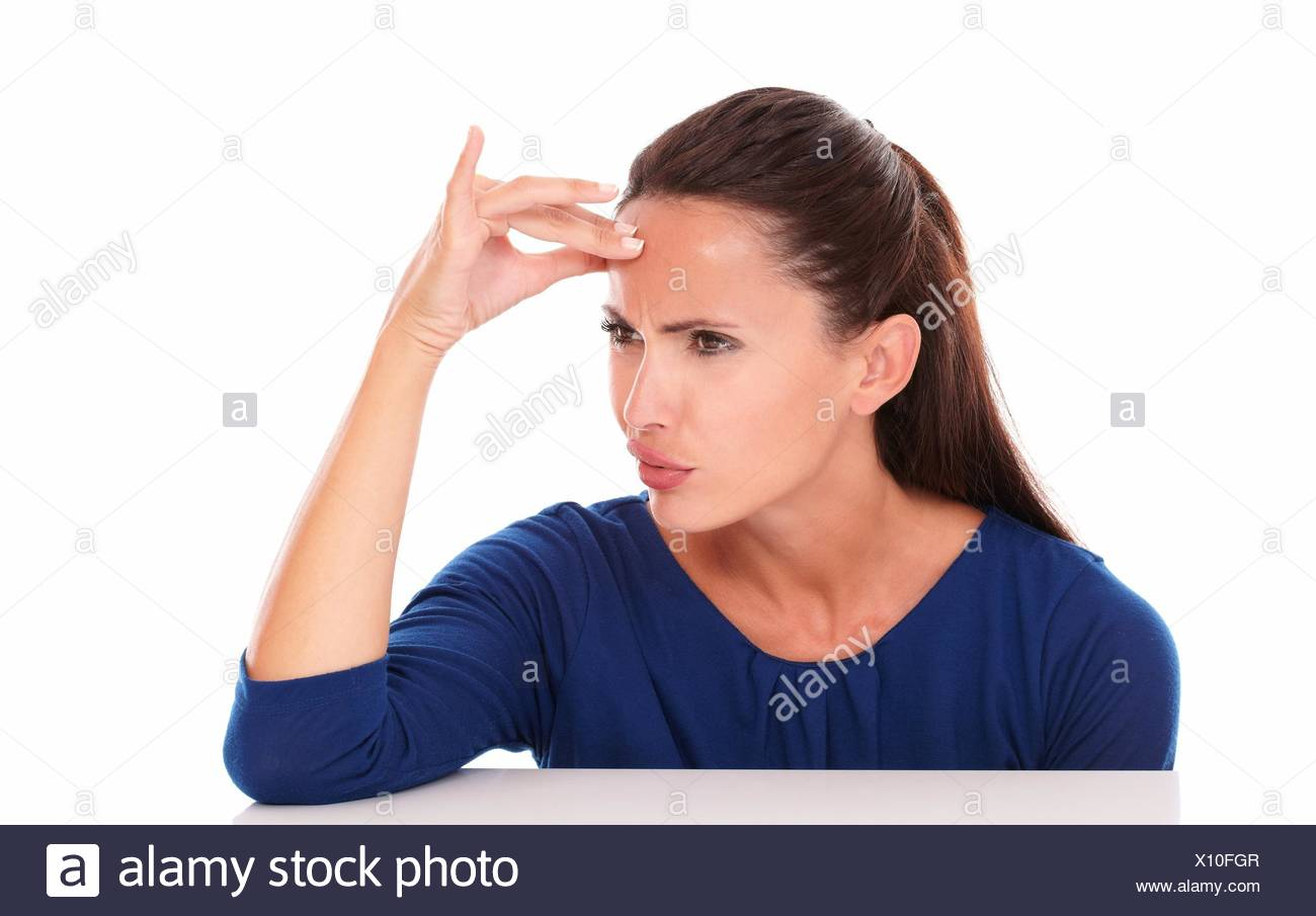 Friendly girl in blue shirt looking embarassed in white background - copyspace. - Stock Image