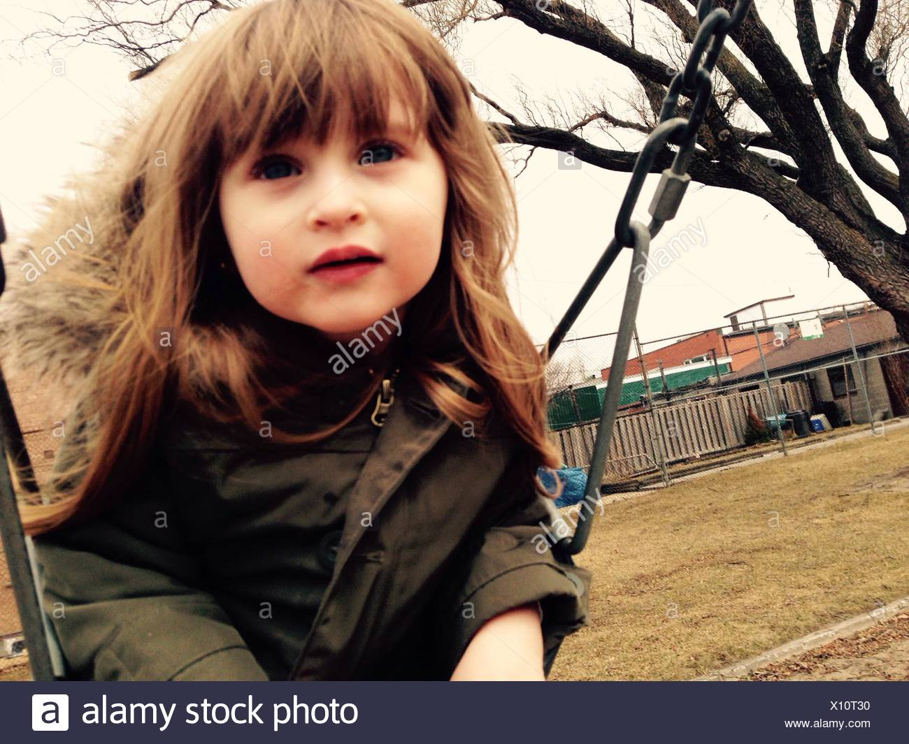 Close-Up Of Girl Sitting On Chain Swing Ride - Stock Image
