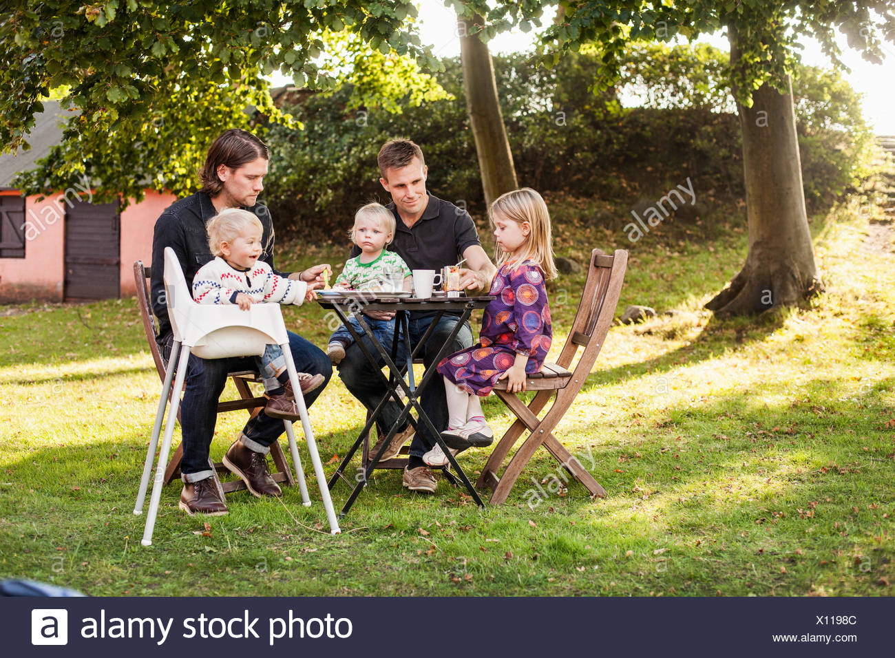 Full length of fathers feeding children in park - Stock Image