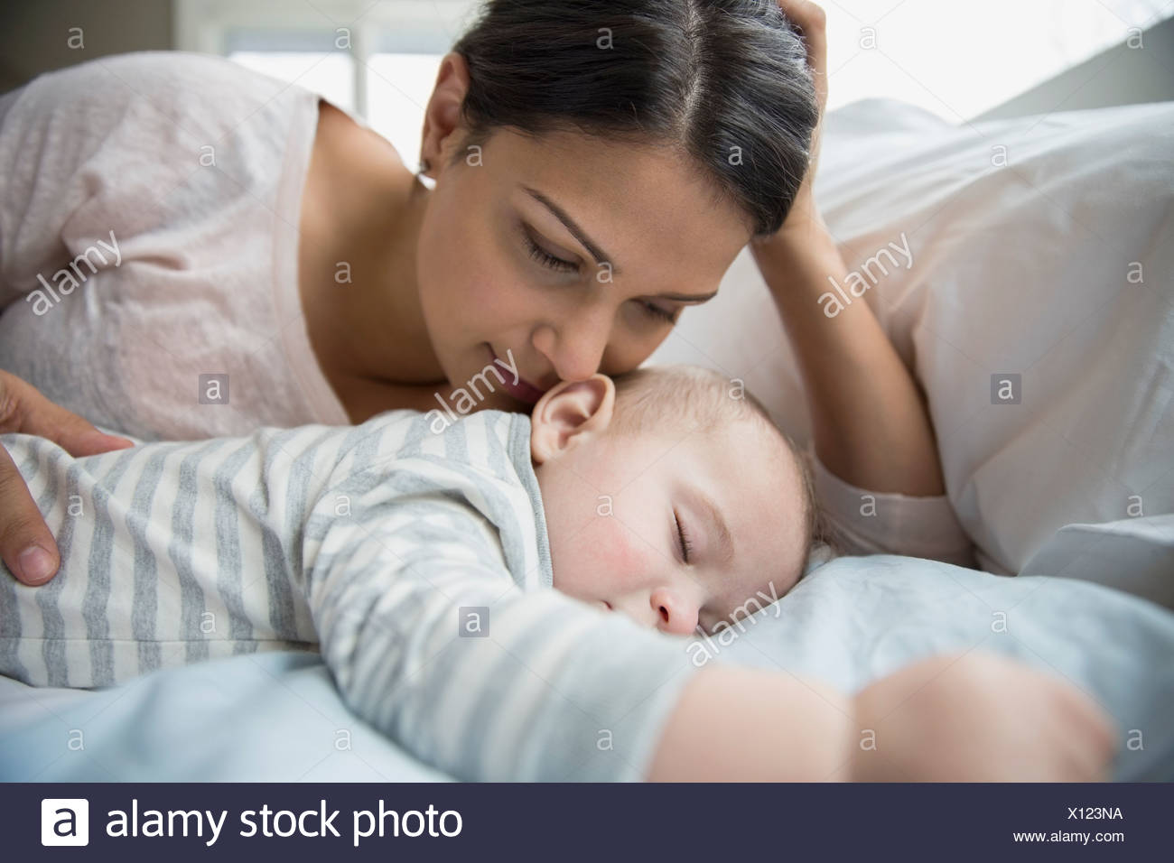 Mother watching sleeping baby on bed - Stock Image