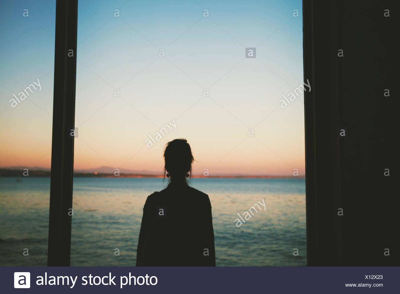 Woman looking at sea through window - Stock Image