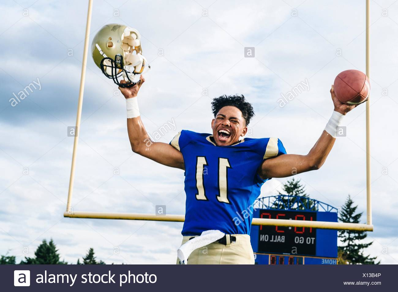Teenage American football player celebrating victory on soccer pitch - Stock Image