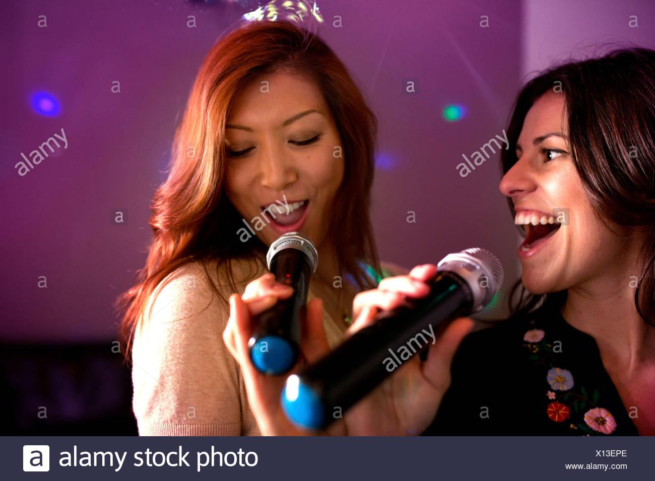 Two women singing karaoke. - Stock Image