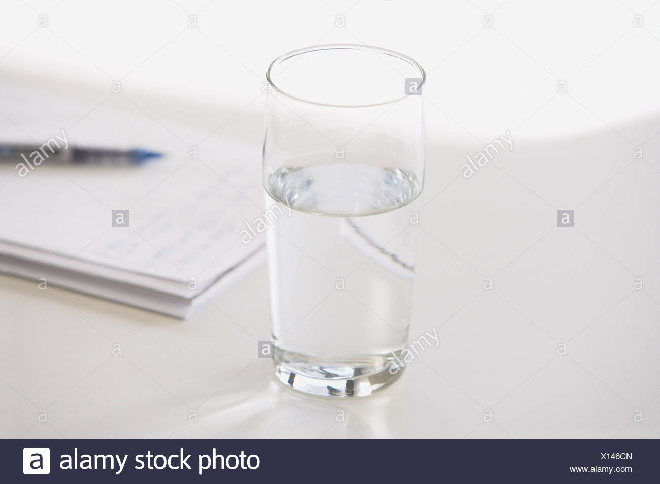 Closeup of glass of water with pen and notebook - Stock Image
