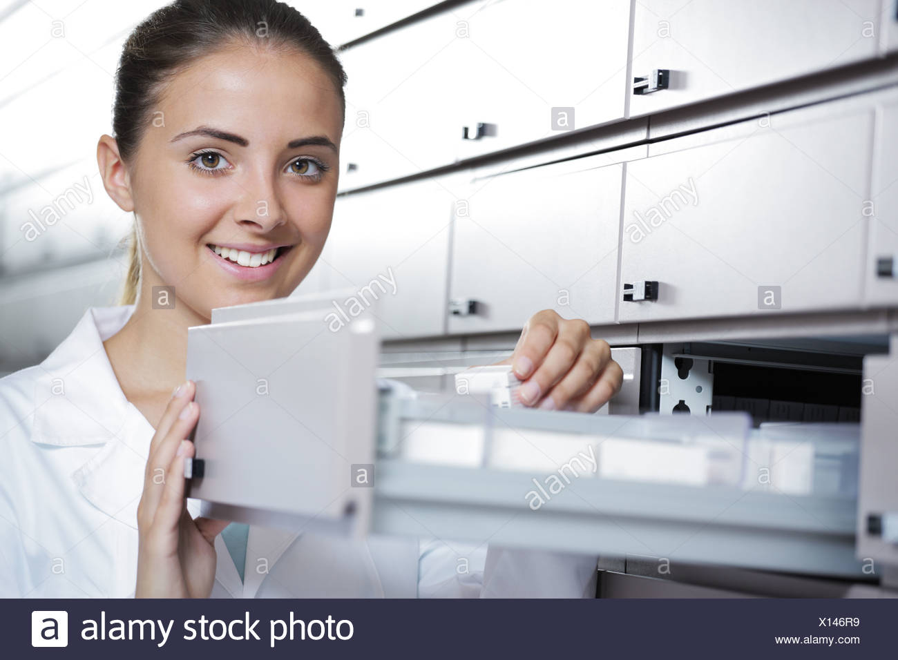 Beautiful young woman pharmacist reaching for medicine - Stock Image