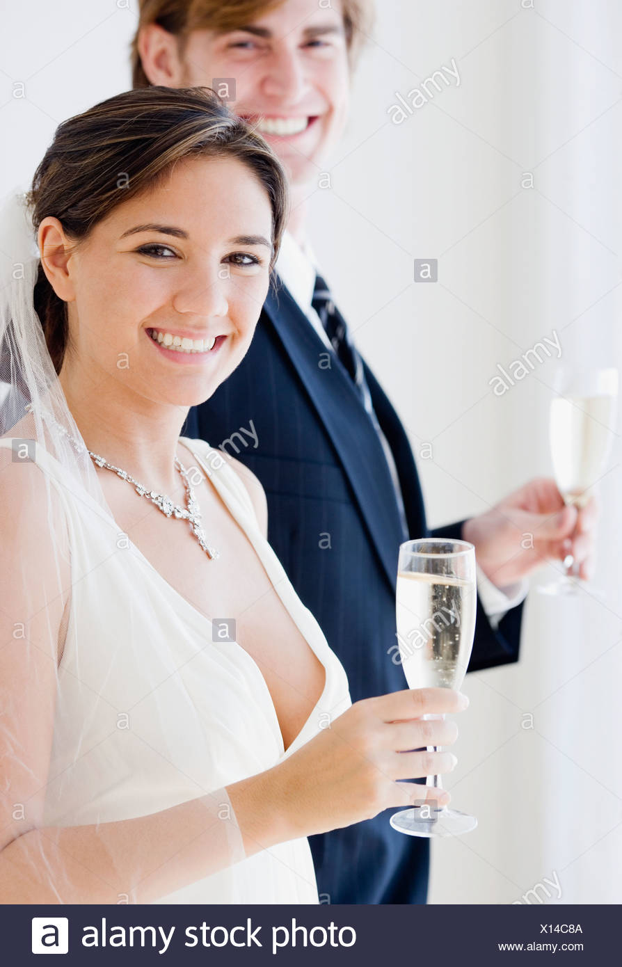 Bride and groom holding champagne glasses - Stock Image