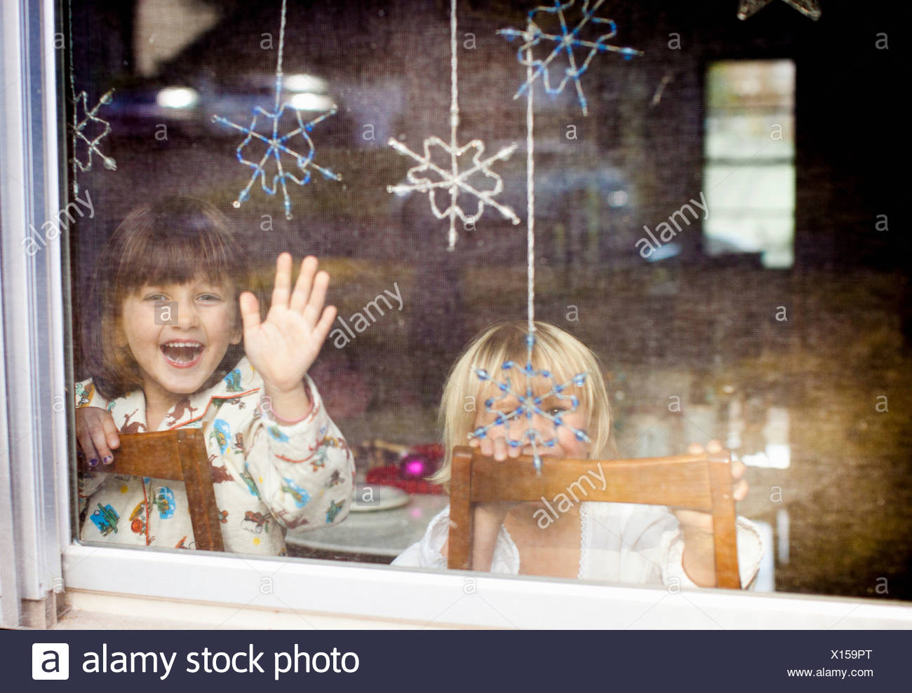 Children laughing and waving at window with dangling snowflakes - Stock Image
