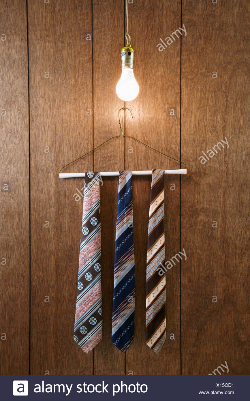 Three Retro Ties Hanging On A Wire Hanger Against Wood Paneling With Wiring Light Fixture Wires Glowing Lightbulb Down From Above
