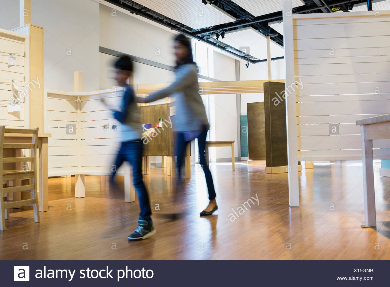 Blurred motion mother and son walking science center - Stock Image