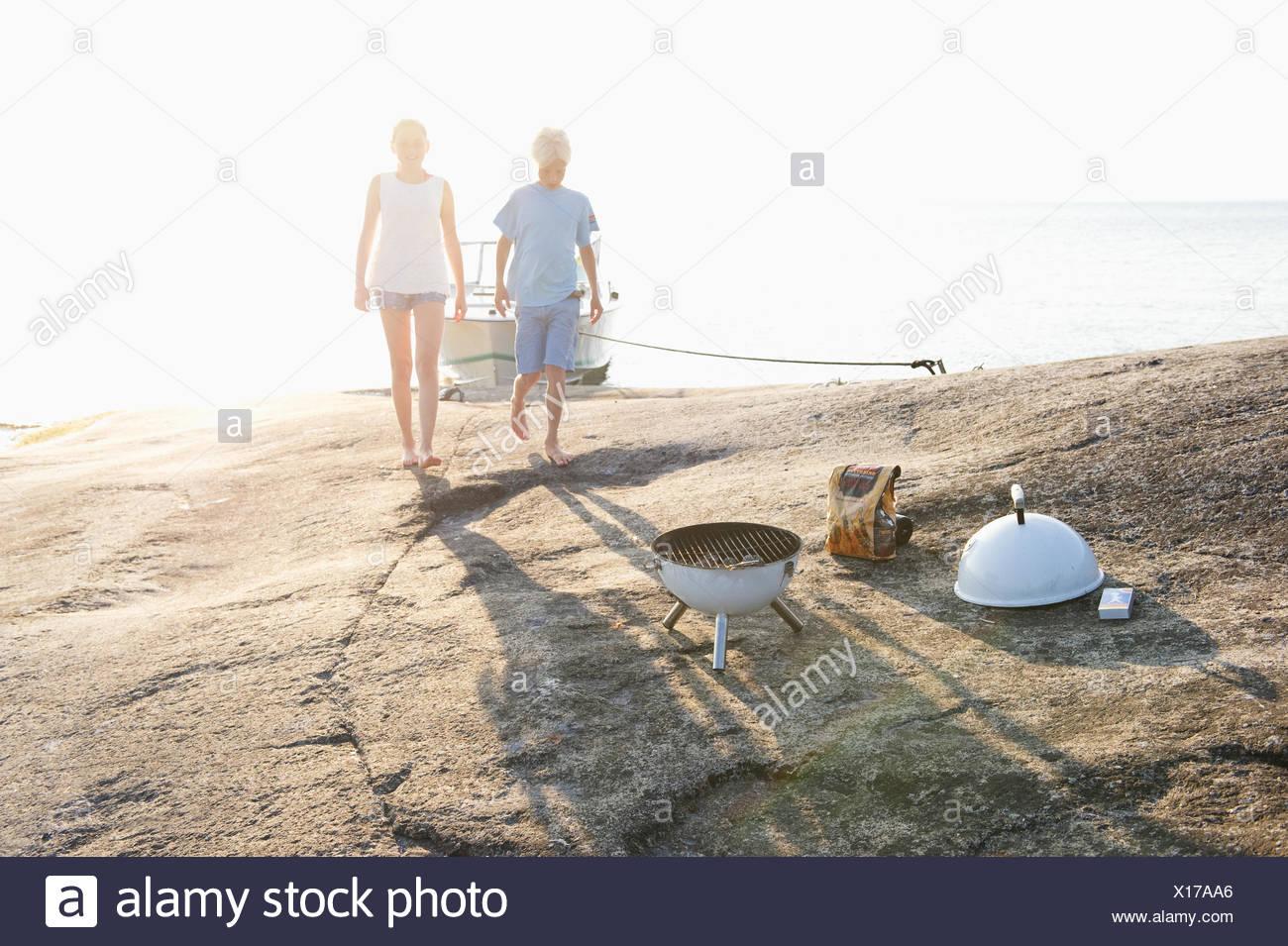 Sweden, Sodermanland, Stockholm Archipelago, Norsten, Boy and girl (12-13) on coastline - Stock Image