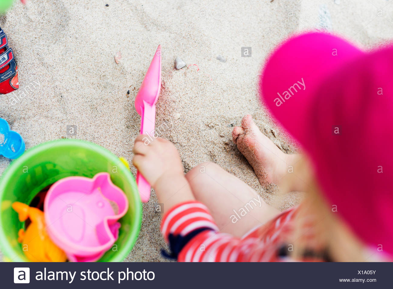 High angle view of girl playing with toys on sand at beach - Stock Image