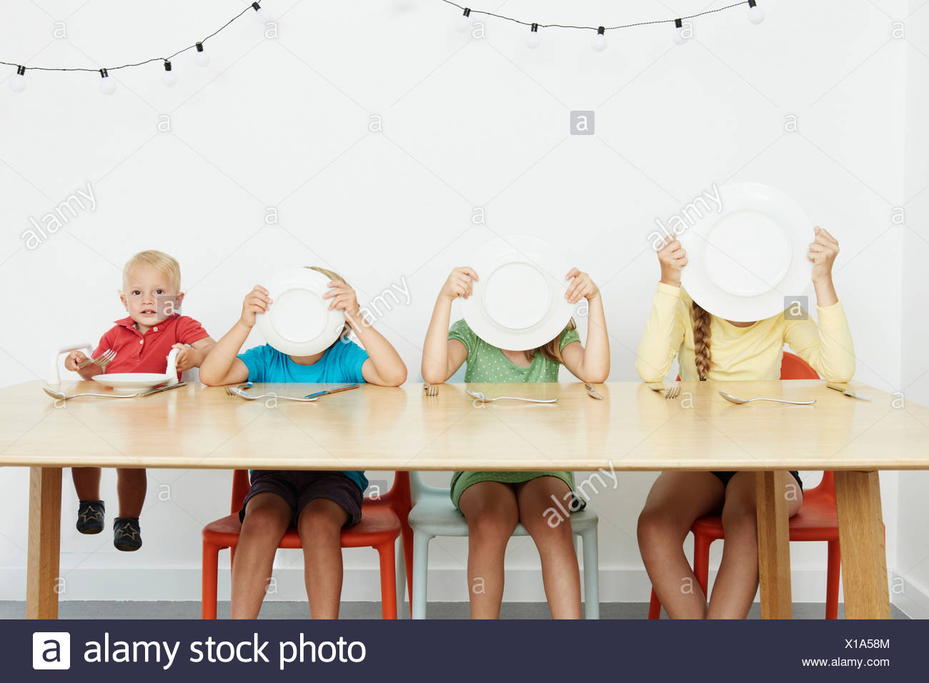 Four children sitting at table, three covering faces with plates - Stock Image
