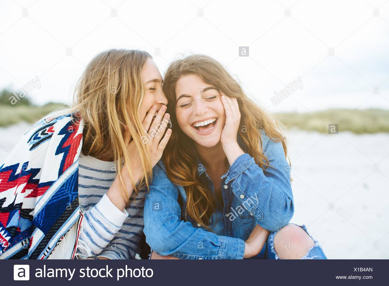 Two young female friends whispering on beach - Stock Image