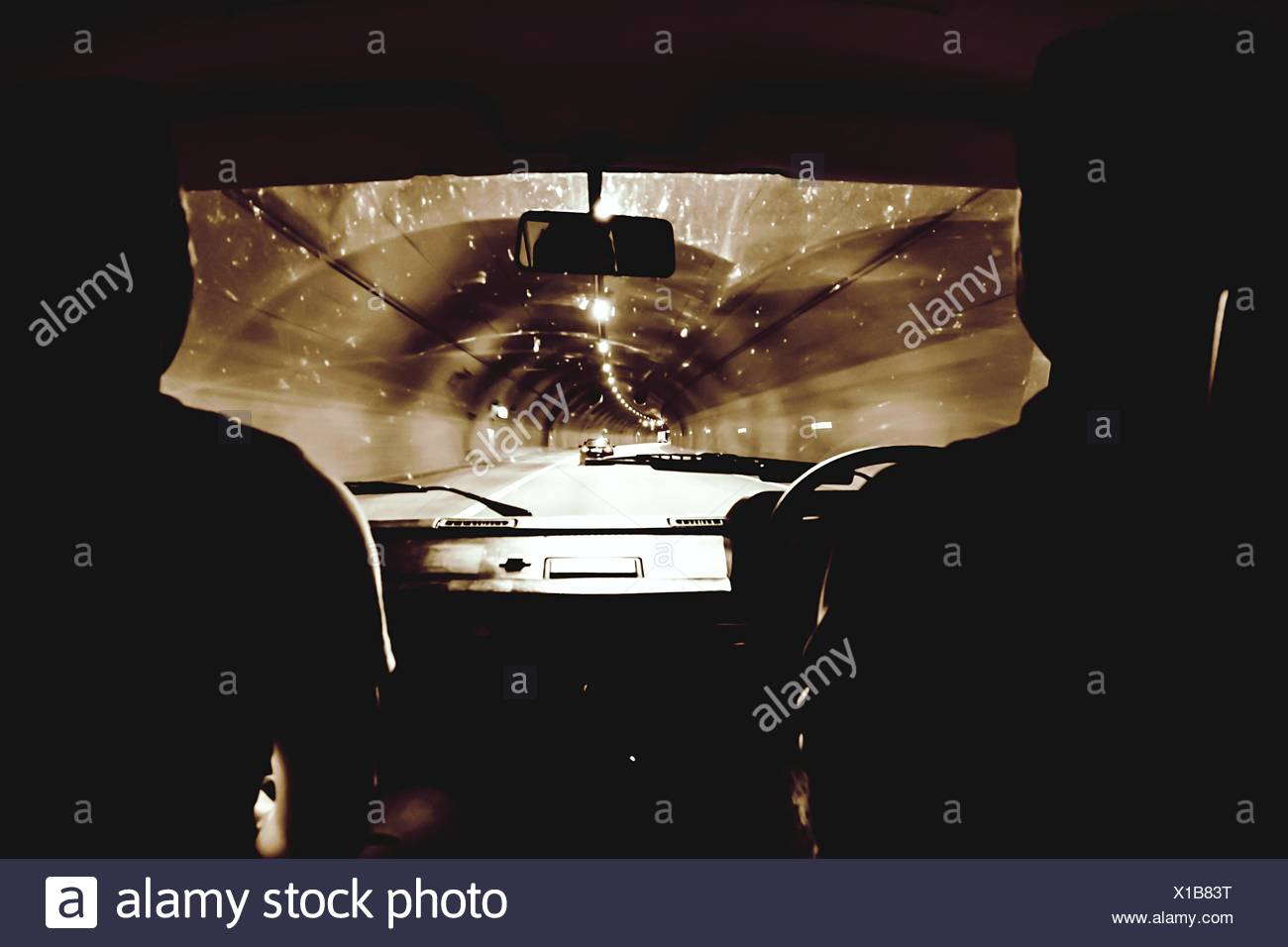 Silhouette People Driving Car In Illuminated Tunnel - Stock Image