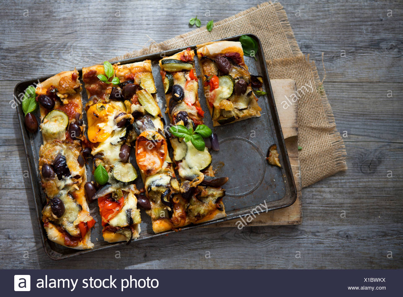 Homemade Roasted Vegetable Pizza with Olives, Basil and Peppers, Sliced - Stock Image
