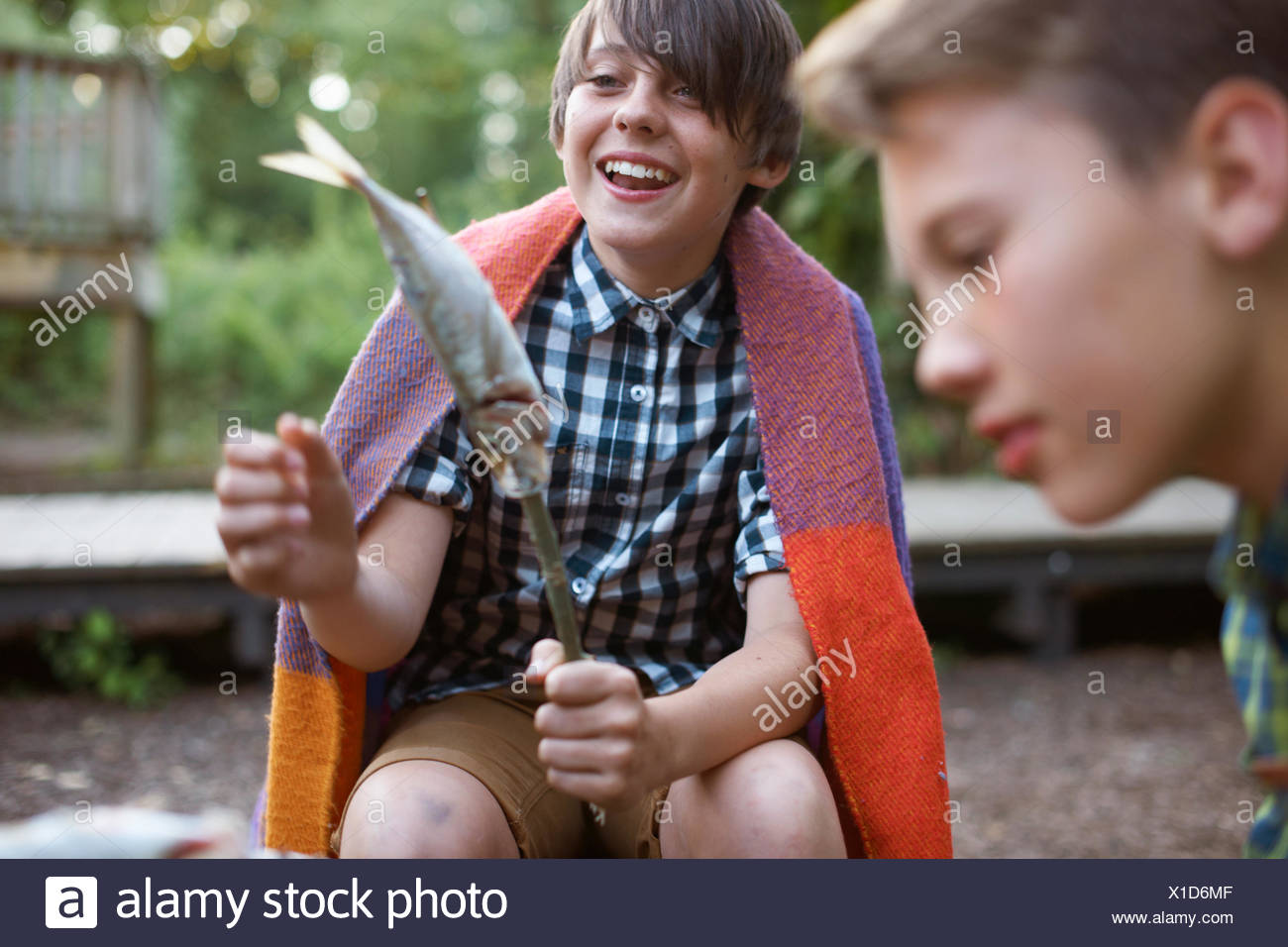 Young boy holding stick with fish on ready to barbecue - Stock Image
