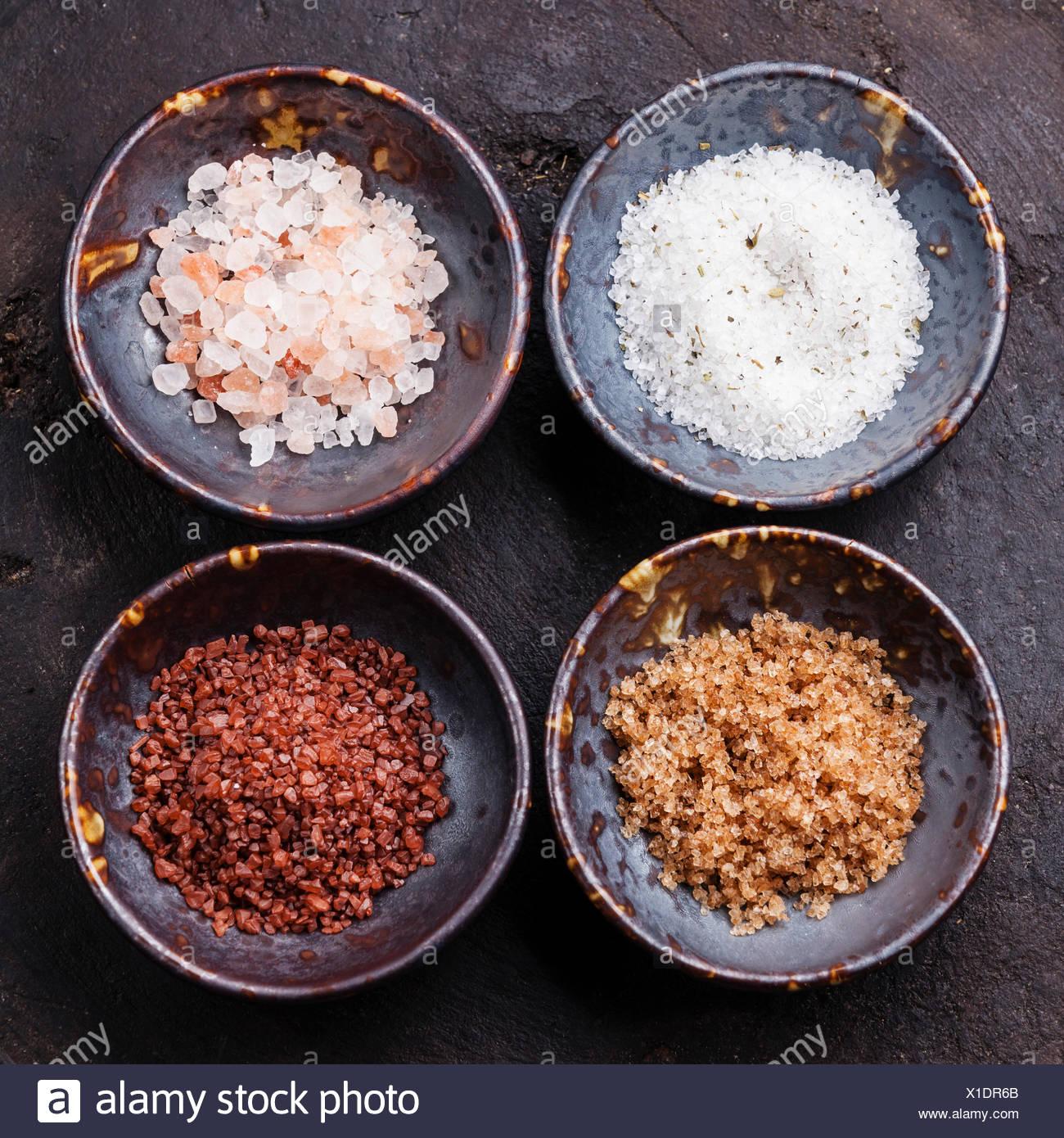 Different types of food coarse Salt in ceramic bowls on dark background - Stock Image