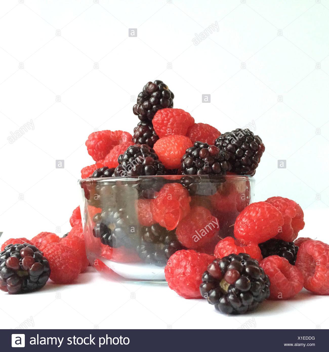 Glass bowl of raspberries and blackberries - Stock Image
