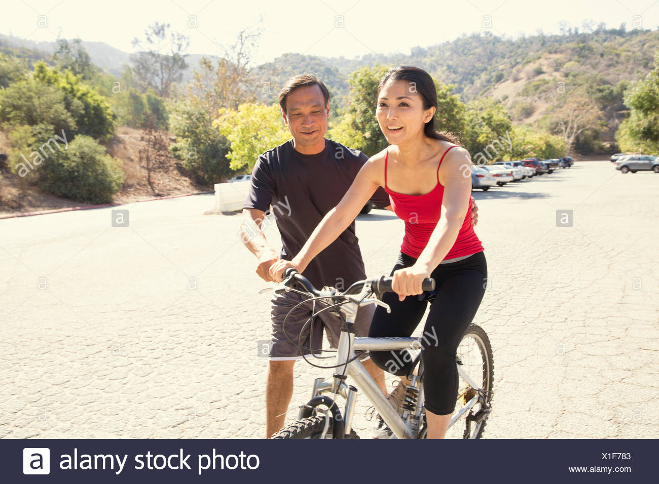 Mature woman learning to ride bicycle in park - Stock Image