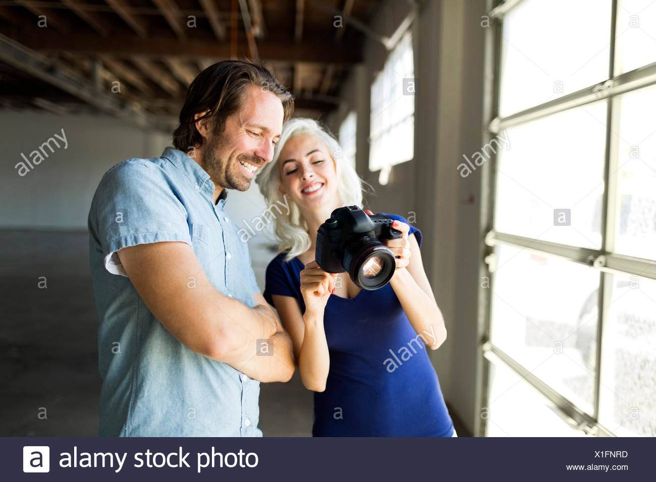 Woman and man looking at pictures in digital camera - Stock Image