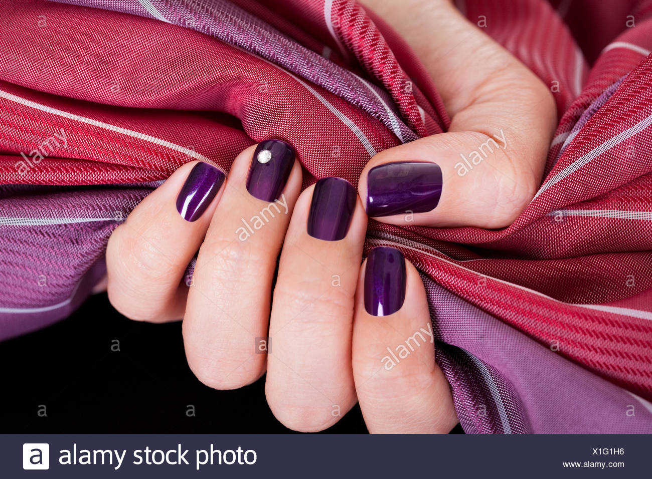 Woman with beautiful purple nails gripping a color matched maroon ...