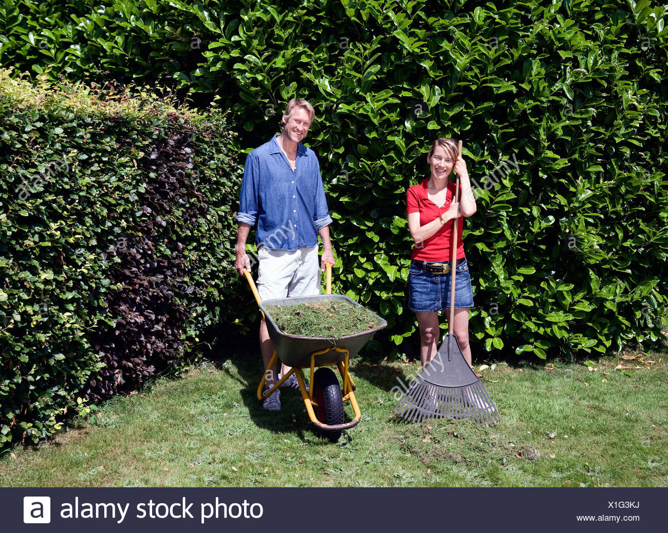 Portrait of couple with garden tools - Stock Image