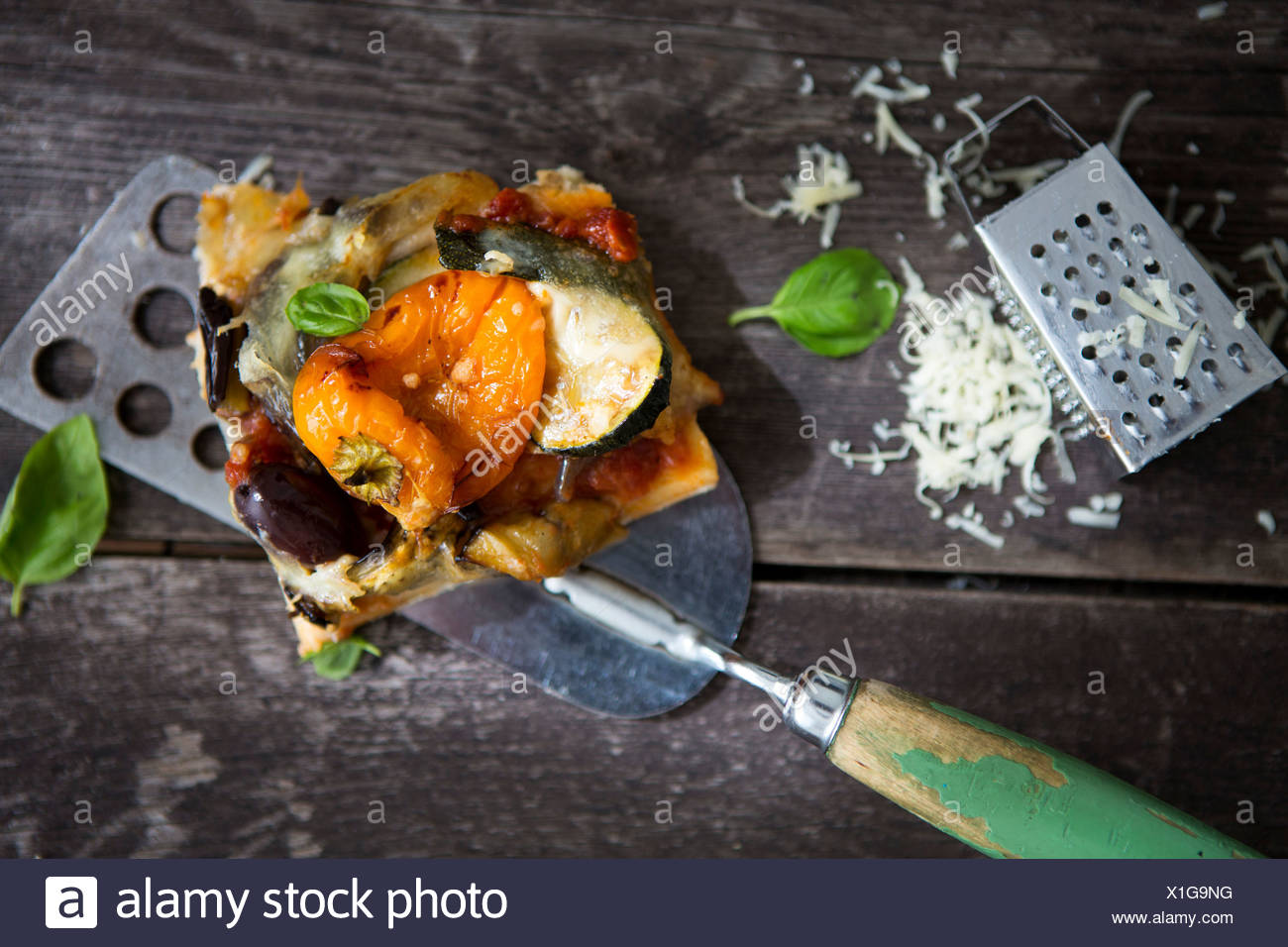 A slice of homemade pizza with pepper, courgette, olive and basil and a cheese grater - Stock Image