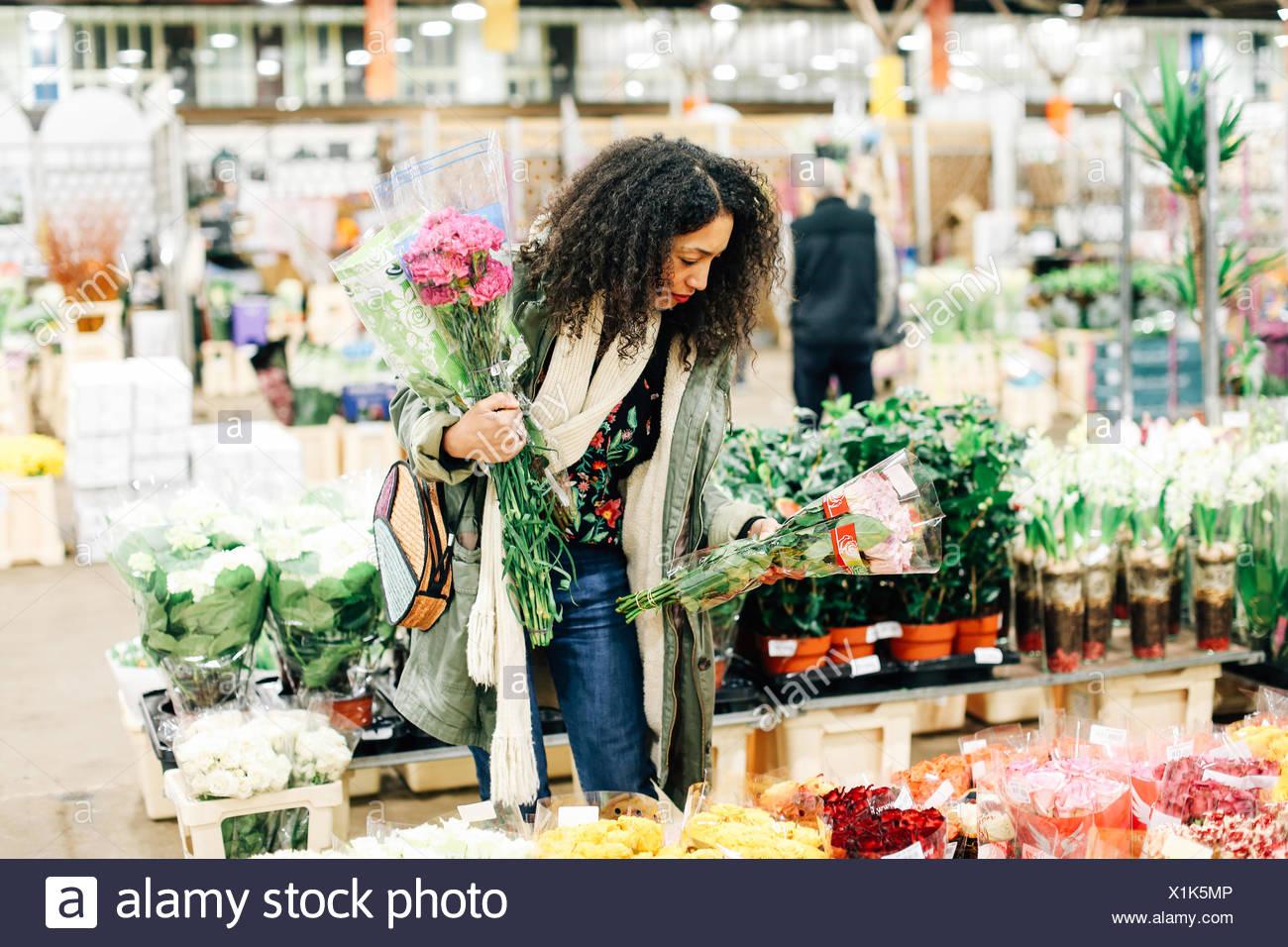 Female florist selecting flowers at new Covent Garden flower market, London, UK - Stock Image