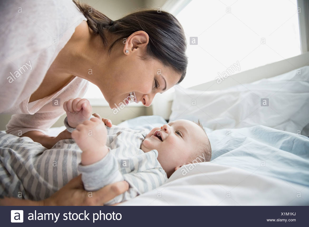 Mother and baby on bed - Stock Image