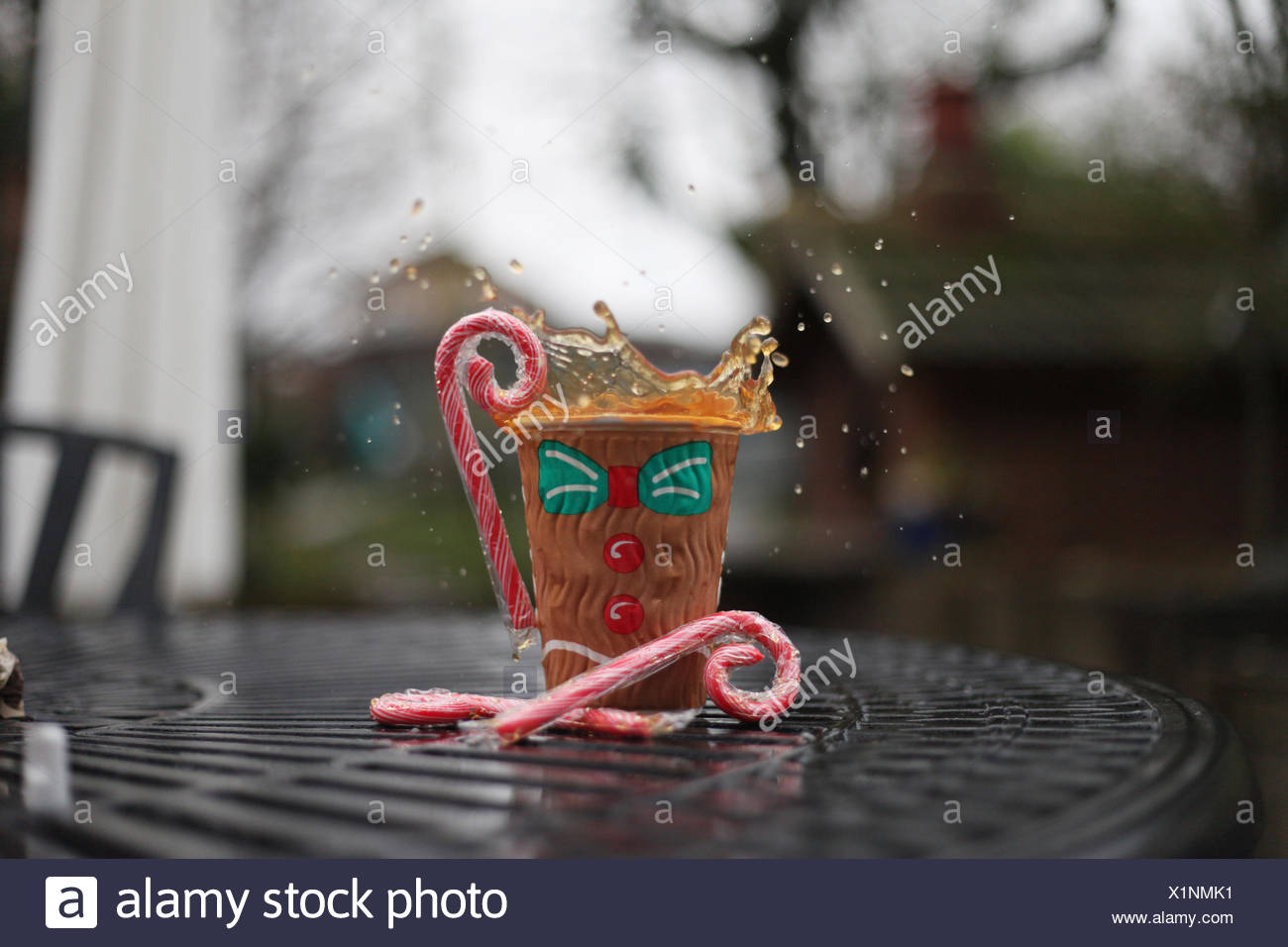 UK, Christmas Goodies! Splash of tea, surrounded by candy canes - Stock Image