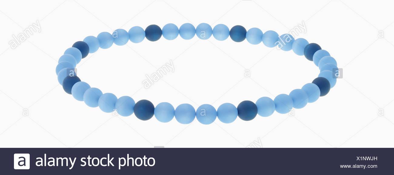 Bracelet of blue beads against white background, close up - Stock Image