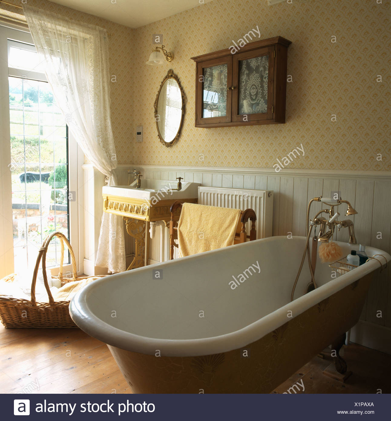 Roll-top bath in traditional bathroom with patterned wallpaper and ...