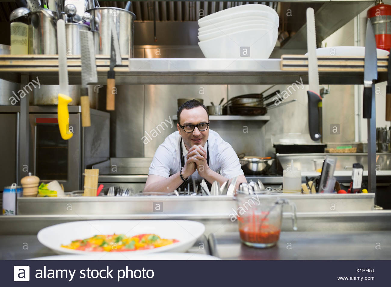 Chef leaning on counter in commercial kitchen - Stock Image