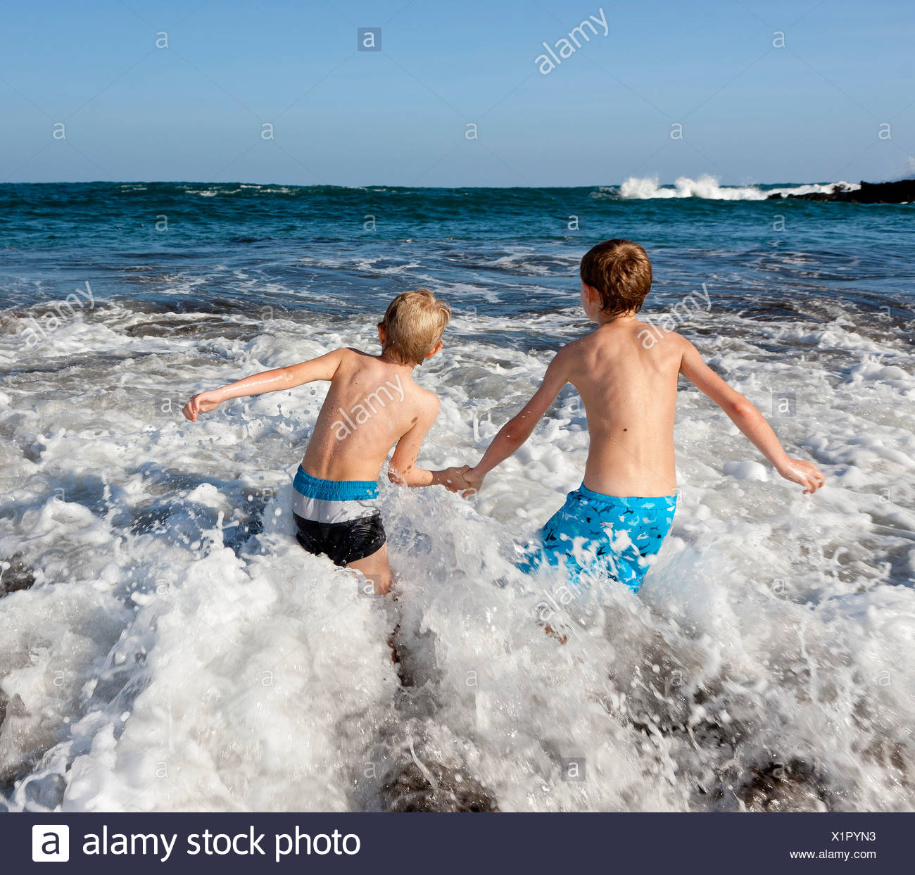 Children playing in the surf, Playa Jardin beach, Puerto de la Cruz, Tenerife, northern part, Canary Islands, Spain, Europe - Stock Image
