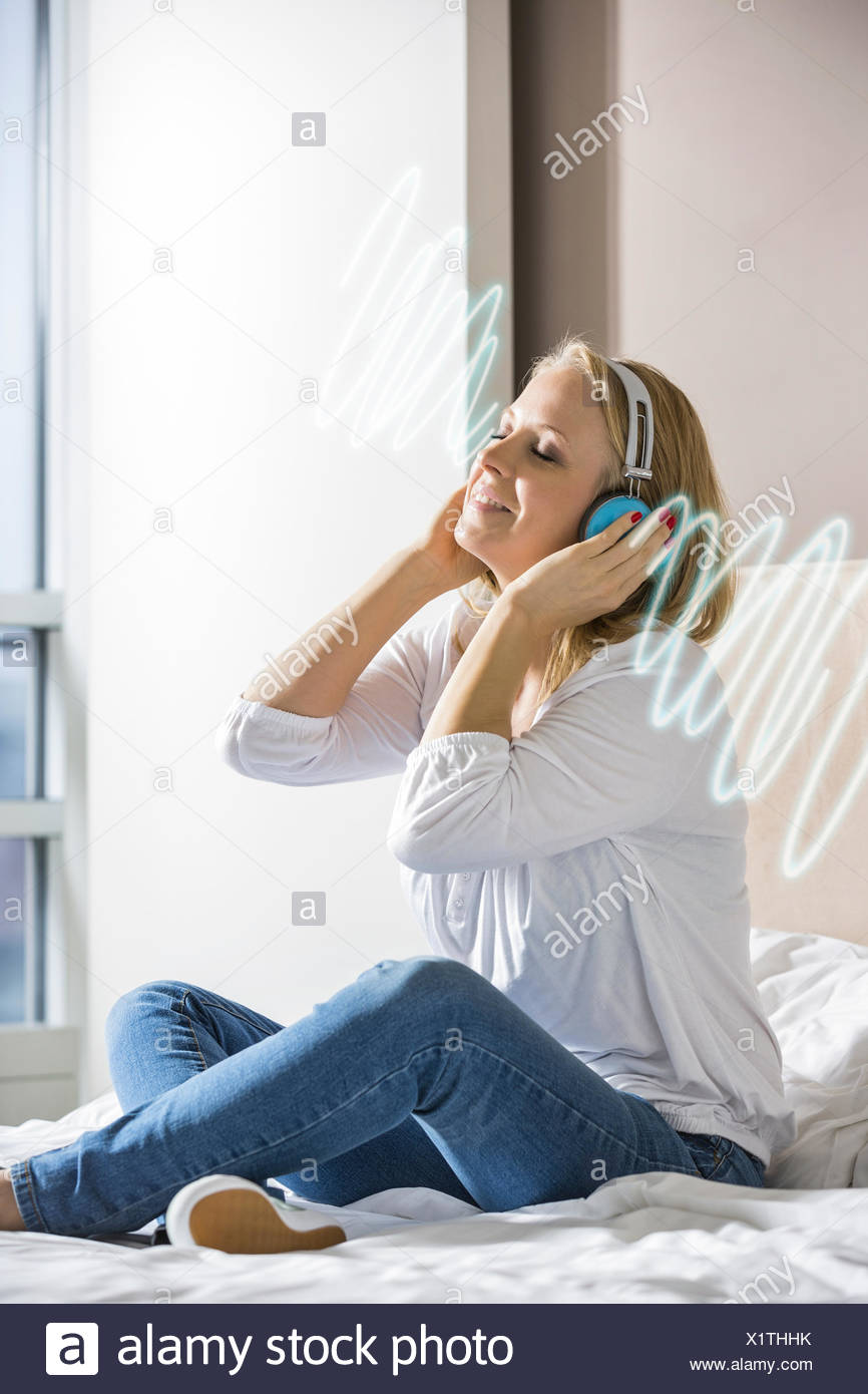 Relaxed mid adult woman listening music through headphones on bed - Stock Image