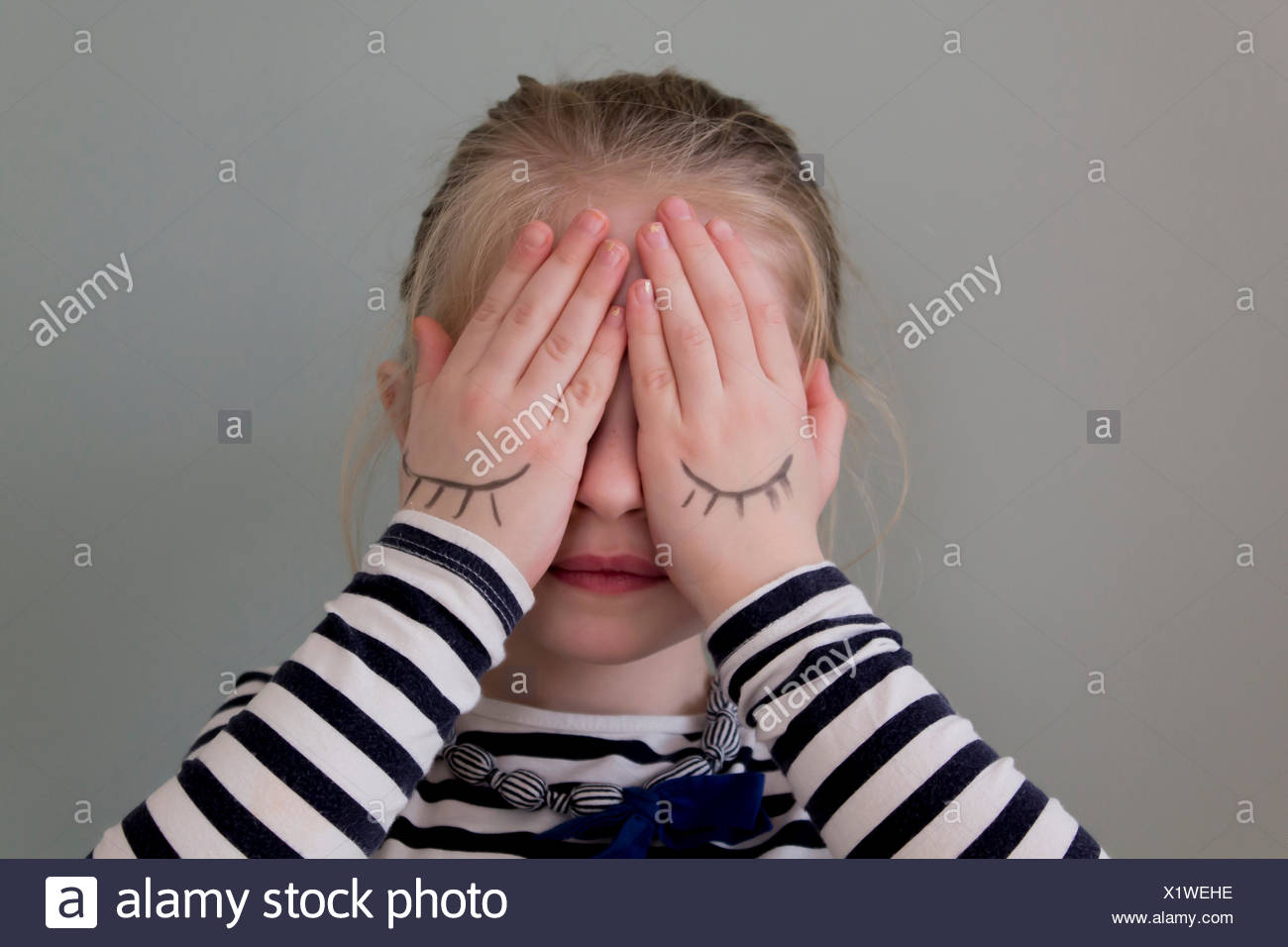 Girl covering her eyes with hands that have eyes drawn on them - Stock Image