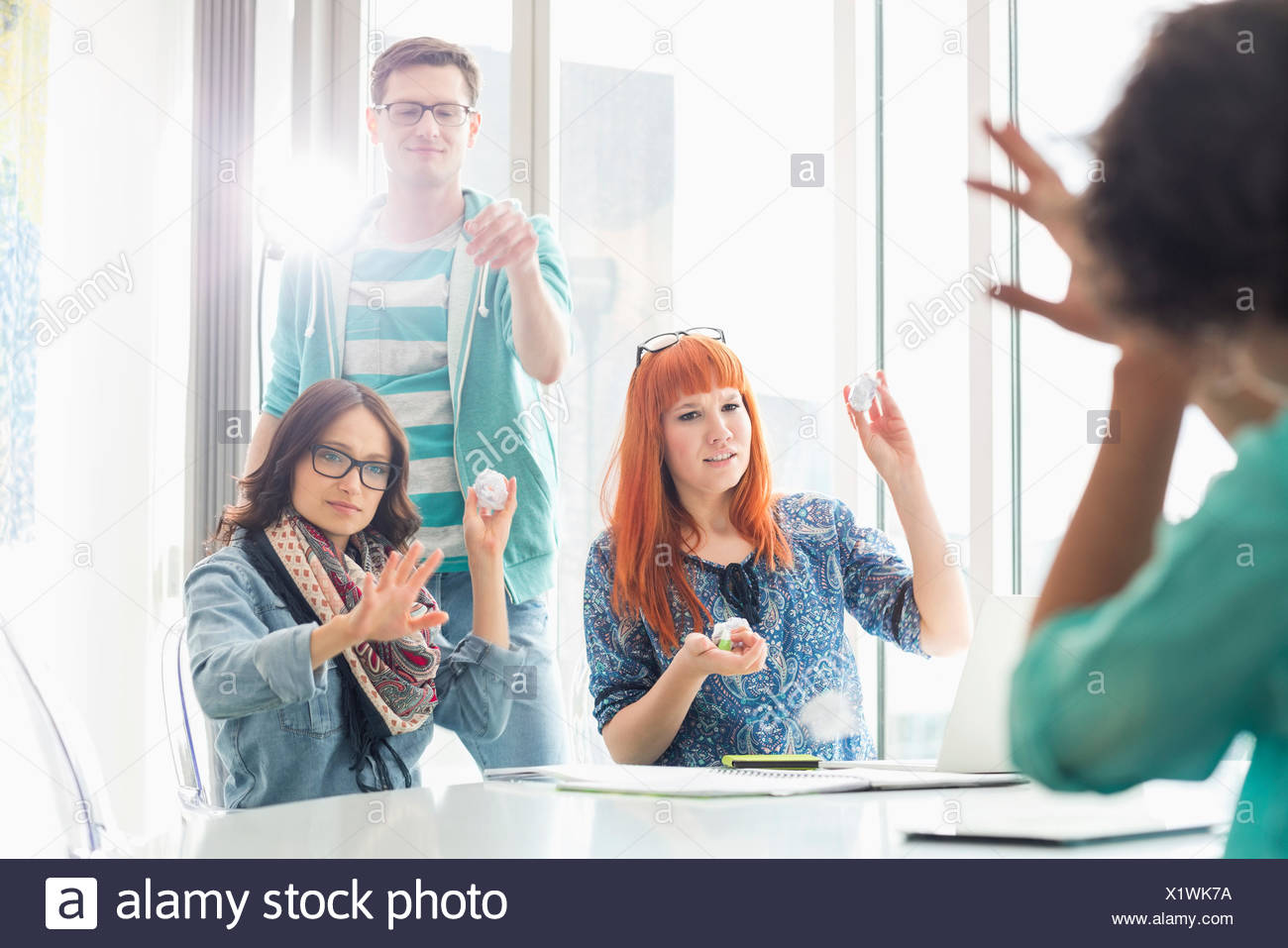 Angry businesspeople throwing paper balls on colleague in creative office - Stock Image