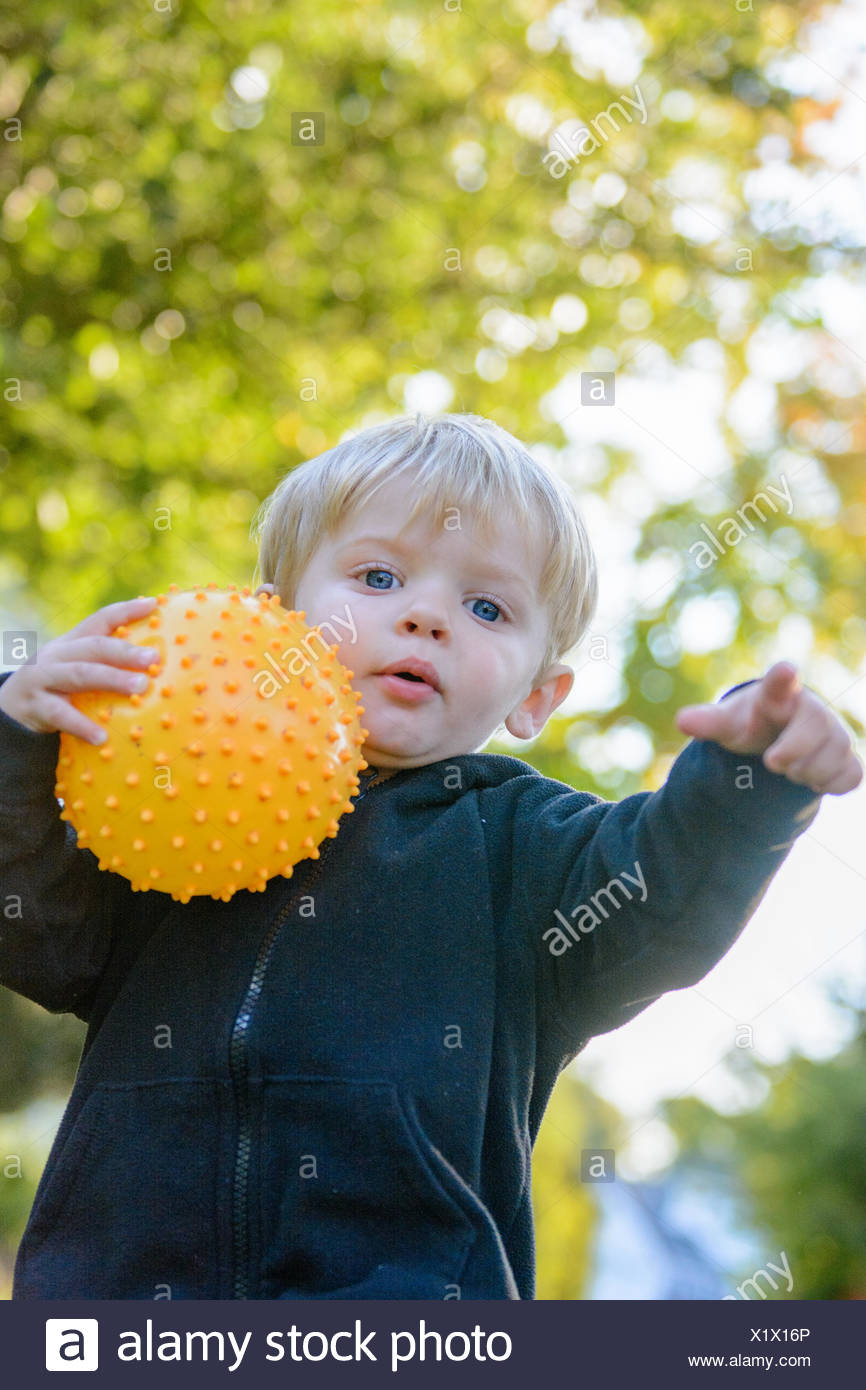 Boy in a park holding a ball - Stock Image