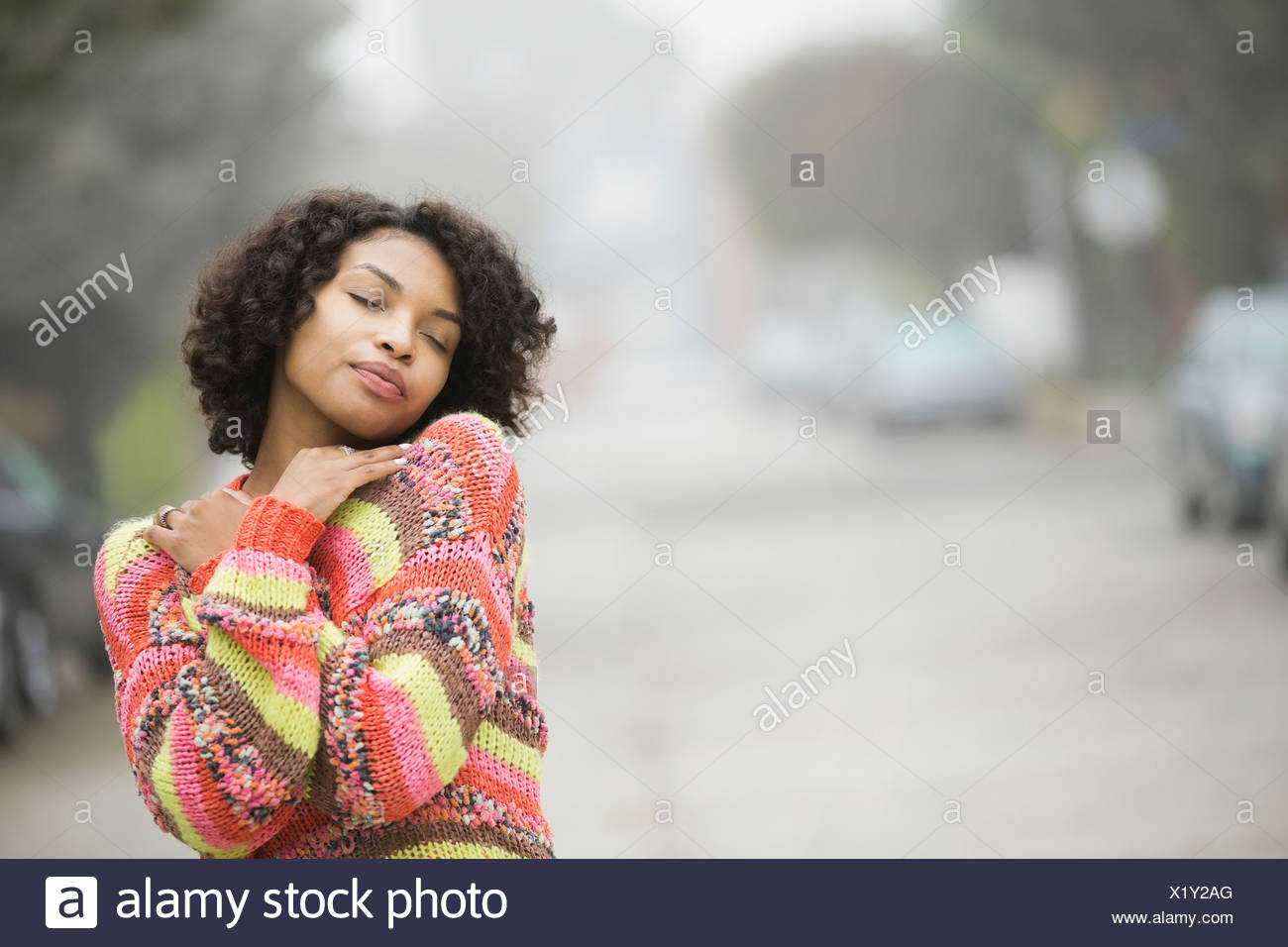 Woman standing outdoors with arms crossed - Stock Image
