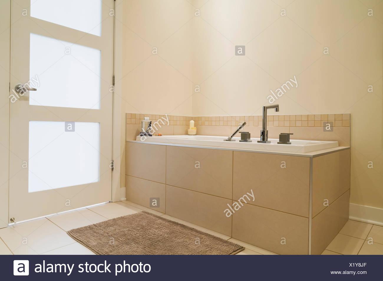 Soaking Tub Encased In A Ceramic Tile Base In Bathroom Of Renovated